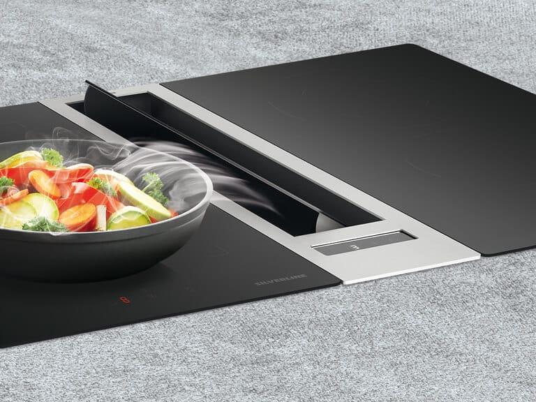 Randabsaugungsplatte nach rechts gekippt, verstärkt die Sogwirkung auf linker Kochfeldseite